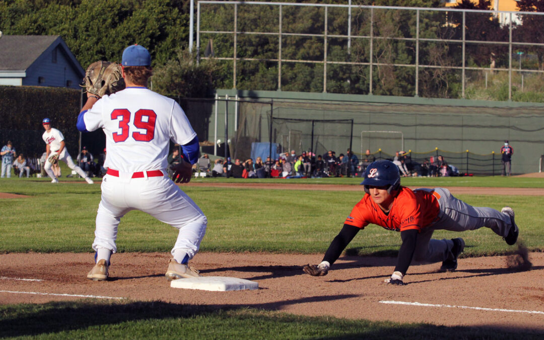 Aidan Morris waits for the ball as the baserunner dives back to first.