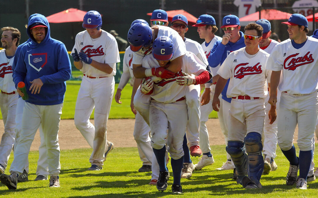 Teammates mob Ethan Fischel after his walkoff hit in the 13th inning.